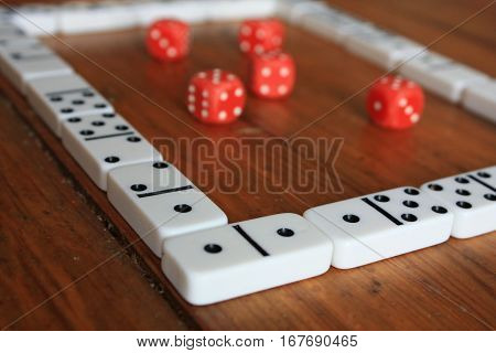 Close up domino game pieces frame with red poker dices inside on brown wooden background