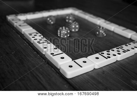 Square shape of domino game pieces and poker classic dices on wooden table in black and white style