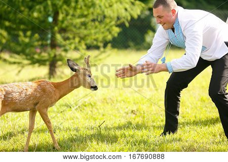Boy in embroidered blue shirt plays with a little deer in the wood
