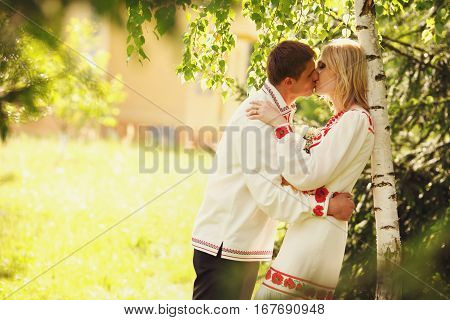 Man In Embroidered Shirt Kisses A Lady Tenderly Leaning Her To The Birch