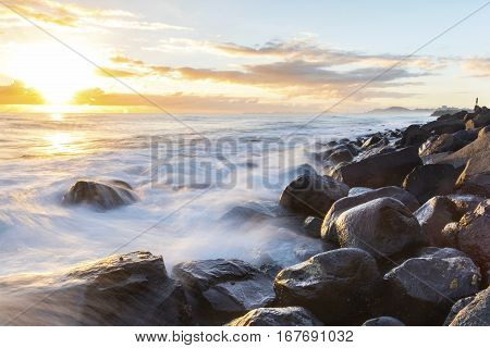 A person watching the sunrise and ocean tide rushing over the rocks at Bureleigh Heads Gold Coast.