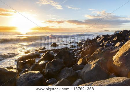 A person watching the sunrise and ocean tide from the rocks at Bureleigh Heads Gold Coast.