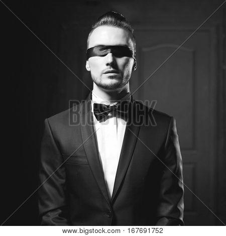 Portrait of stylish man in elegant black suit with blindfold