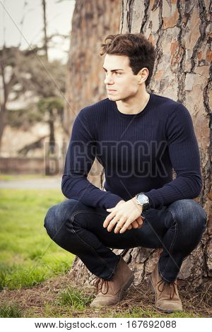 Young man model in a park under a tree. A beautiful and charming young man sits at the foot of a tree in a squat position in a park with green grass. He wears a dark blue long-sleeved shirt, blue jeans and tan shoes.