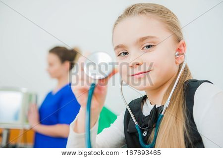Caucasian Girl Playing Doctor Using Stethoscope in the Doctor Office.