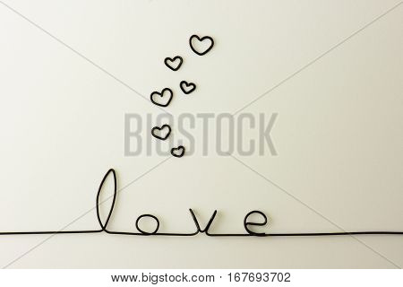 """Cute and simple """"LOVE"""" background with rising hearts, made from black wire. Natural white background."""