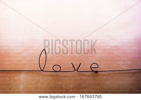 """The word """"Love"""" made from black wire, on retro amber background fading in to white."""