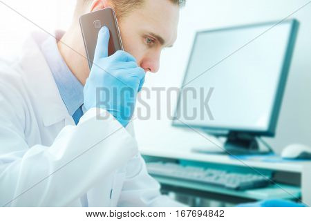 Doctor Phone Call Consultation. Medical Doctor Using His Phone and Computer To Get Second Opinion. Mid 30s Caucasian Doctor.