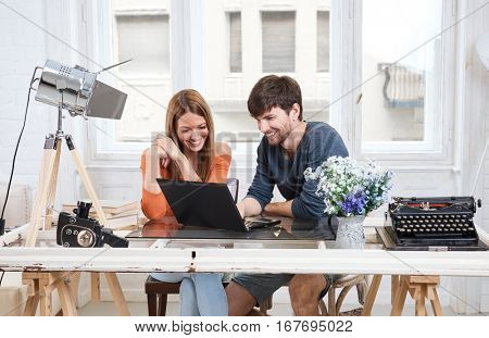 Young couple sitting at desk at home, using laptop computer, smiling happy.
