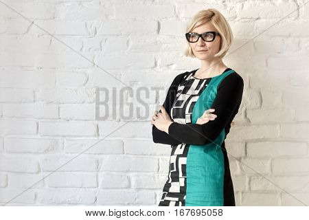 Old-fashioned woman standing arms crossed front of white brick wall.