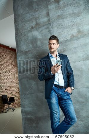 Caucasian businessman using mobile phone leaning against wall smiling.