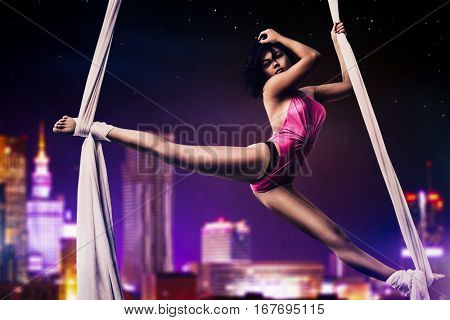 Young woman gymnast on night modern city background