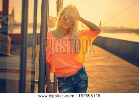 Young teenage style woman with sunglasses standing on stone quay at morning sunrise