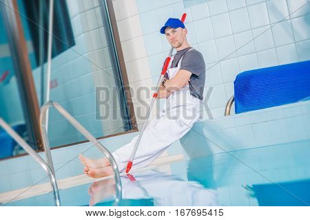 Swimming Pool Technician Cleaner Taking Rest Break On the Edge of Large Indoor Pool.