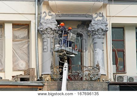 Moscow Russia - October 03 2016: Workers paint columns with stucco on the facade of the house on Tverskaya in Moscow.