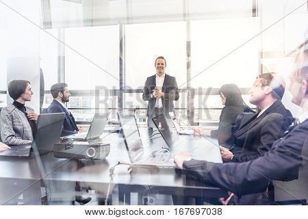 Successful team leader and business owner leading informal in-house business meeting. Business people working on laptops in foreground and glass reflections. Business and entrepreneurship concept.