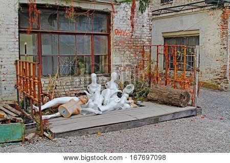 Group of discarded nude mannequins in junkyard.