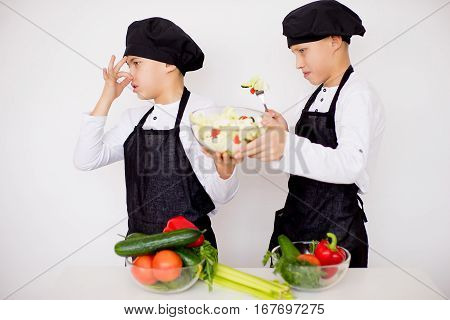 two young chefs near the white table evaluate a salad isolated. disgusting