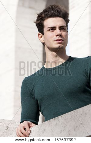 Stylish hair young man outdoors on the ledge, tight knit. A beautiful young European (Italian) man is outdoors resting on the ledge. The boy wears a tight knit long-sleeved green.