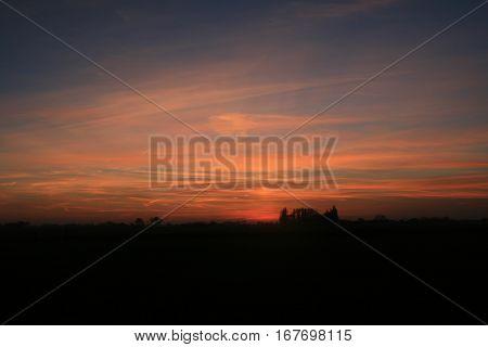 zonsondergang met heel veel kleurschakeringen en silhouet van bos