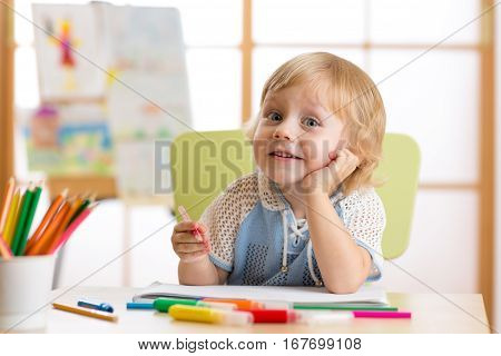 Smiling kid having an idea while drawing in his room