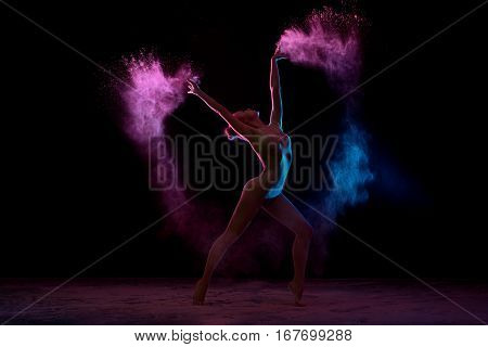Young girl in beige bodysuit dancing in cloud of pink and blue dust bending and raising her hands gracefully up studio shot
