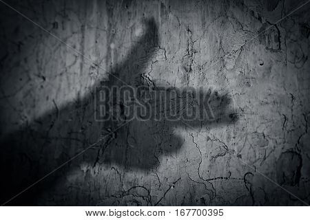 Shadow of gun created with human hand on the rough wall.