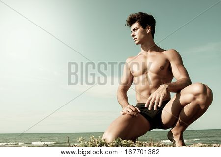 Young man naked on his knees. Sea and sky behind. A young man with a beautiful body is on his knees with the sea behind. Intense light and color antiqued.