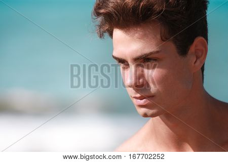 Beautiful and young man shirtless portrait. A beautiful young Italian man posing at the sea shirtless, serious and sure of himself.