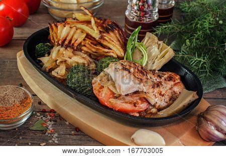 chicken fillet stuffed with tomato, grilled onions and cheese with vegetables broccoli, artichoke, fried potatoes and green onions in a pan served on the village