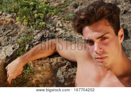 Beautiful portrait young man shirtless outdoor on the rocks. A handsome young Italian man posing at the sea shirtless on the rocks, serious and sure of himself.