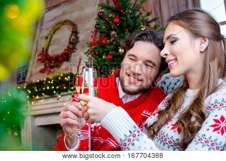 Happy couple toasting with champagne glasses at christmastime