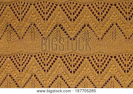 Light brown knitted background with openwork pattern closeup