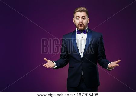 Handsome man in tuxedo and bow tie is surprised and throws his hands. compere in fashionable, festive clothing on dark background