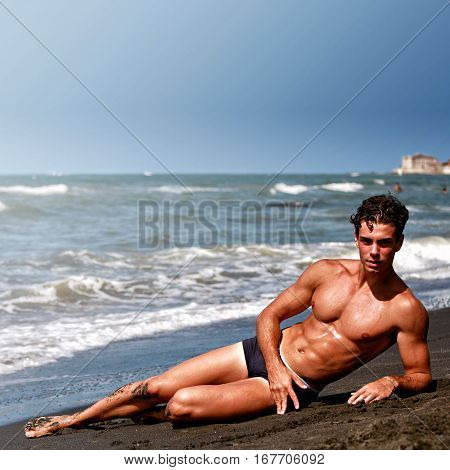 Muscular model young man lying and relaxing, sea shore. A muscular young man relaxing on the shore of the sea. The boy is lying on the left side. Blue sea. Cloudless sky.