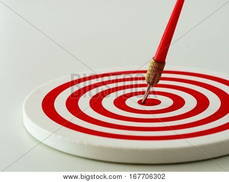 Red bullseye dart arrow hitting target center of dartboard. Concept of success target goal achievement. Vintage with flare tone (selective focus)
