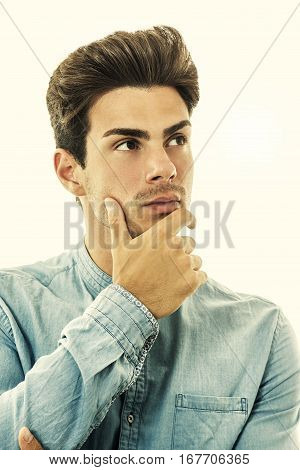 Young handsome man model, doubt and perplexity. A nice boy with a blue shirt has his arms folded and his hand under his chin. Stylish hairstyle.