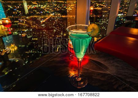 Lowkey lighting and closeup selective focus to Cocktail and lemon on top a small drink after dinner with blur background citynight on skyscraper