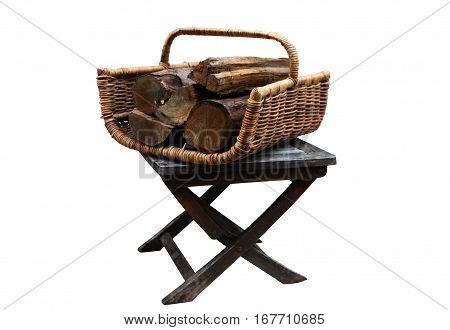 Wicker basket with firewood for the fireplace or wood-burning stove in the old wooden folding chair for garden. White isolated background.