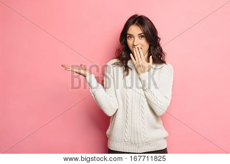 Surprised Beauty funny teenage girl showing empty copy space on open hand palm for text, pink color background. Happy girl Proposing product