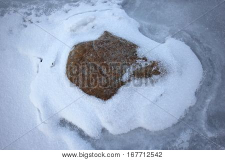 A rock frozen in Lake Michigan with snow around it