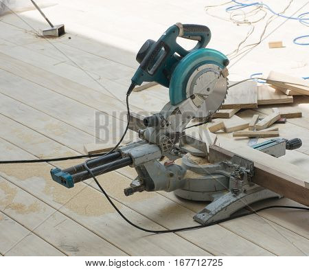 Sawing a circular saw or carpenter tools put on the wooden floor in sunny day.