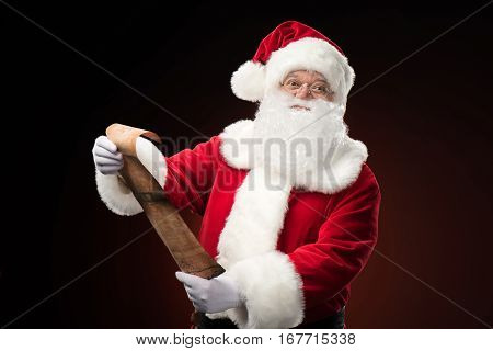 Happy Santa Claus standing with wishlist in hands