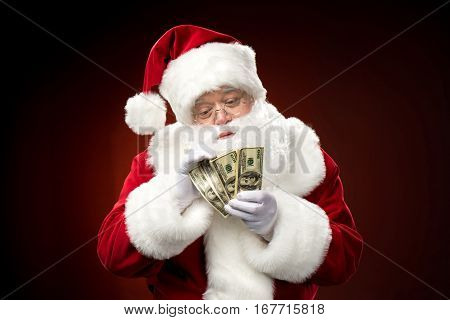 Santa Claus counting dollar banknotes against dark background