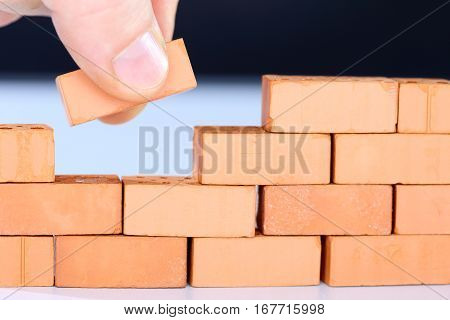 hand is taking the last brick to a wall