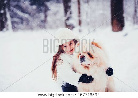 Happy girl hugging a dog in the woods. child and chow chow
