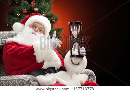 Serious Santa Claus showing hourglass and gesturing Christmas coming