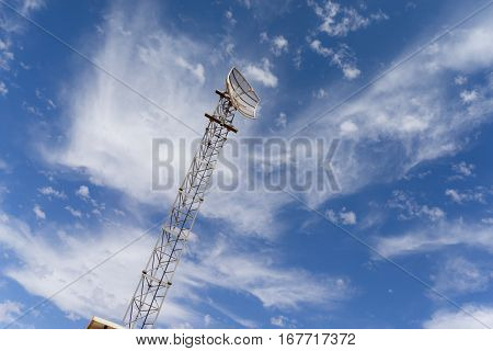 A communication tower with a satellite dish on top stands tall against a blue sky on a sunny day.