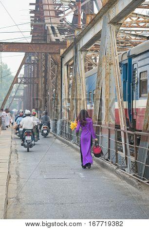 Vietnamese Woman In Traditional Dress Ao Dai Walking On Old Long Bien Bridge, Hanoi City
