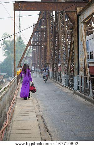 Vietnamese woman in traditional dress Ao Dai walking on old Long Bien bridge Hanoi city poster